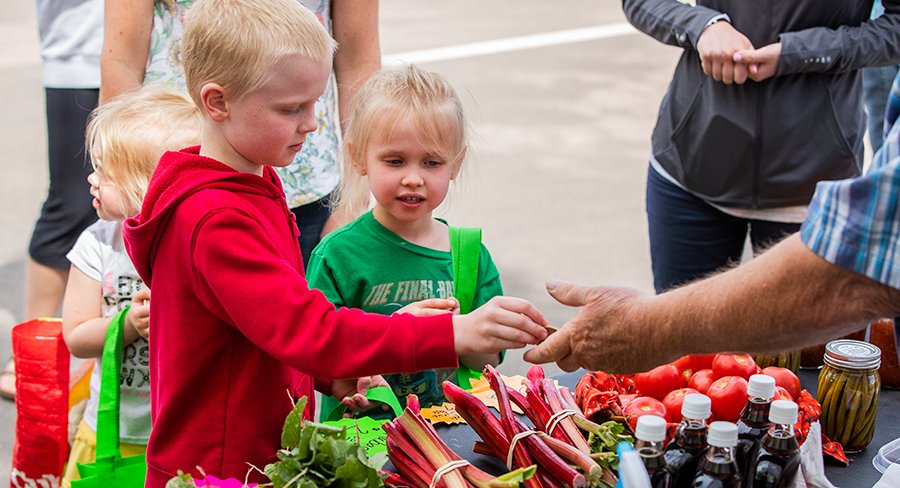 Three kids purchase produce from vendor at Hillside Farmers Market