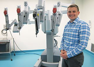doctor standing next to the da vinci robot