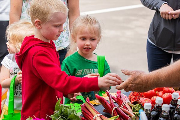 Children exchanging money for food at the Hillside Farmers Market.